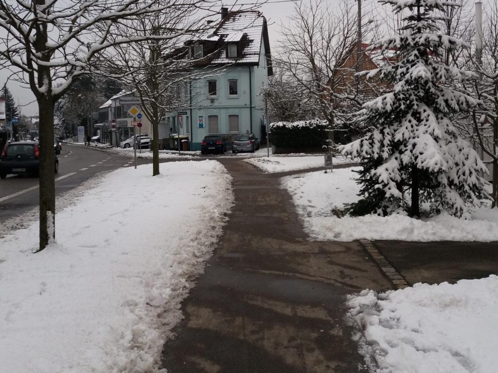 Chão coberto de neve com caminho aberto para passagem de pedestres na calçada.