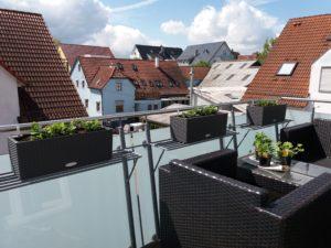 Visão de uma sacada com plantas recém-plantadas. Poltronas, mesa. Se veem telhados, ceú azul com algumas nuvens.