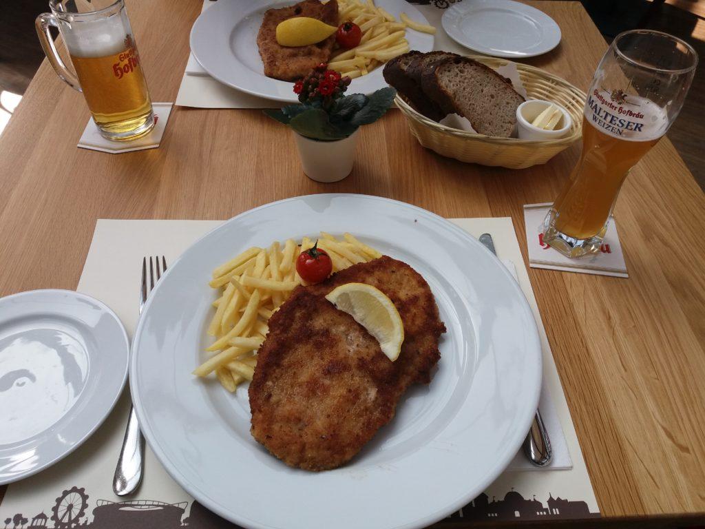 Mesa com um prato servido de schnitzel e batatas fritas, acompanhado de pão e cerveja.