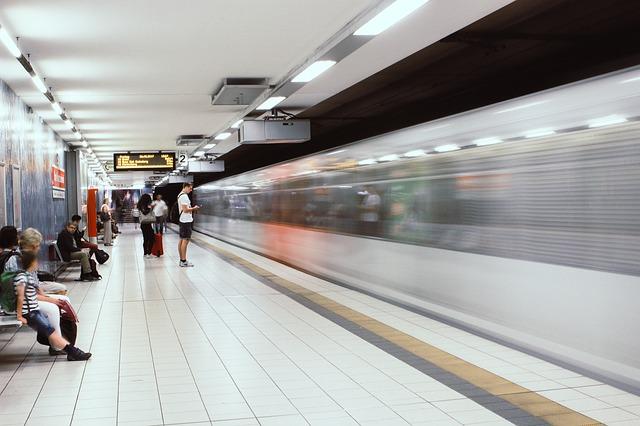Estação de U-Bahn (trem urbano/metrô na Alemanha), com algumas pessoas aguardando o transporte e um trem passando em alta velocidade.