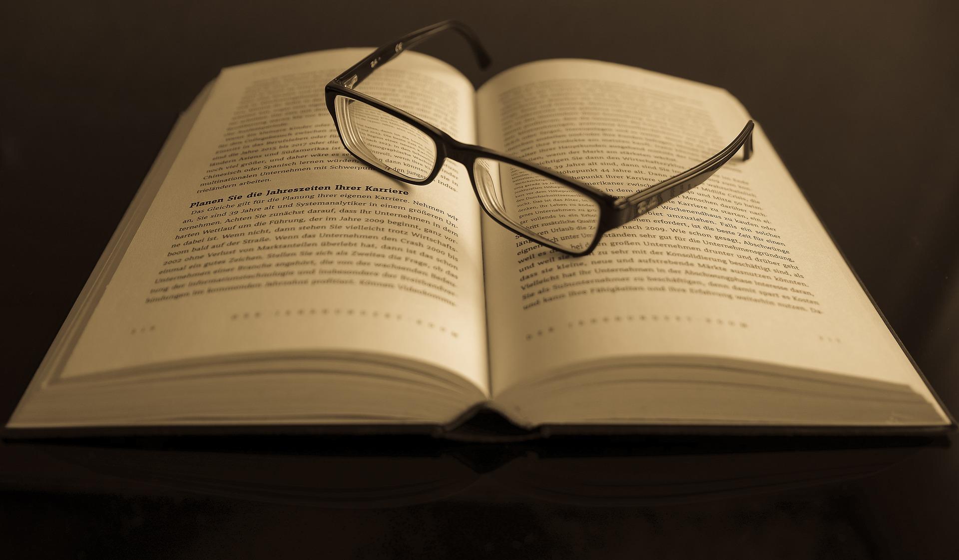 Livro aberto, em alemão, com óculos de leitura sobre ele.