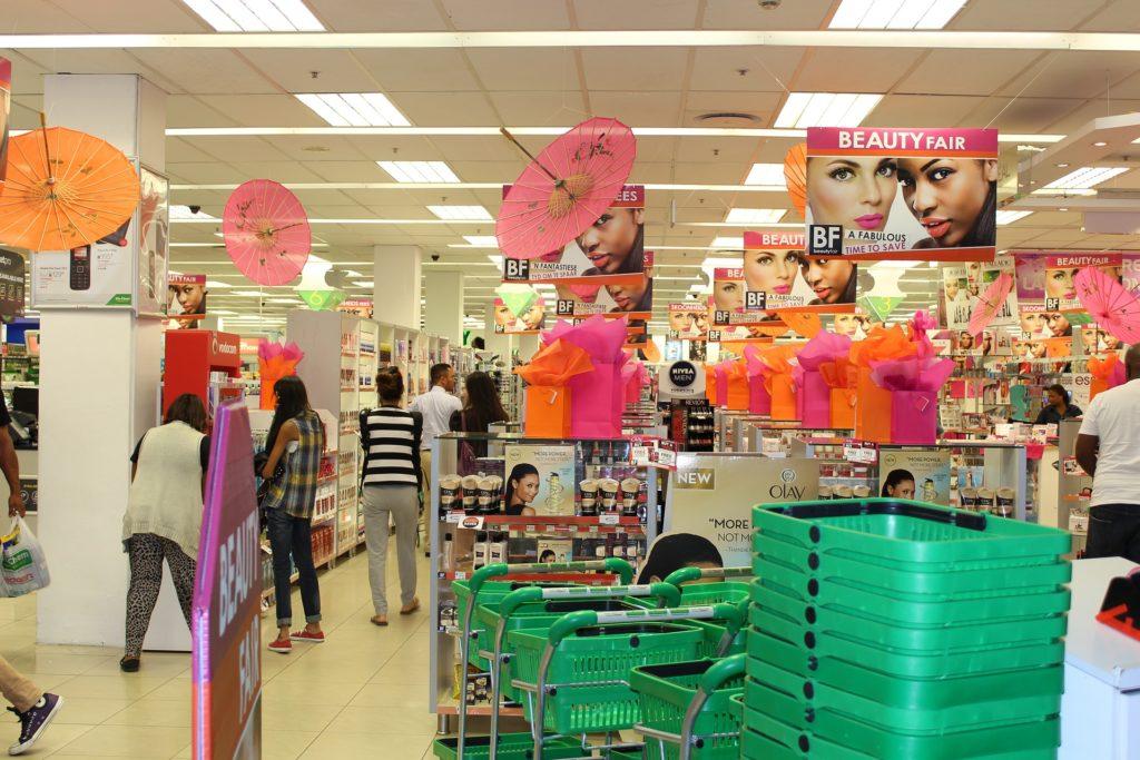 Loja de cosméticos com cestinhas e carrinhos, várias prateleiras com produtos e pessoas comprando.