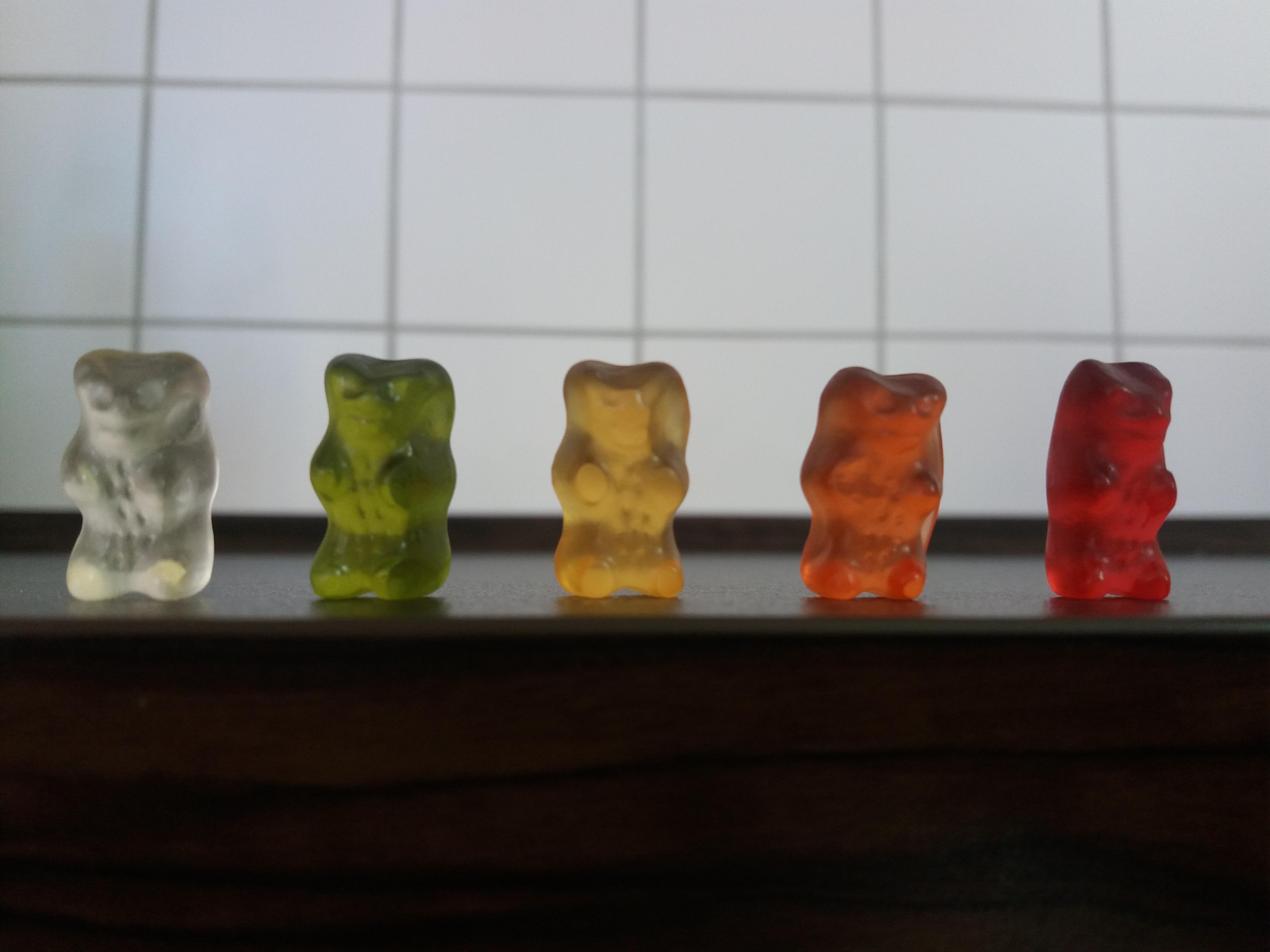 Cinco ursinhos de gelatina, de diferentes cores, enfileirados sobre um balcão.