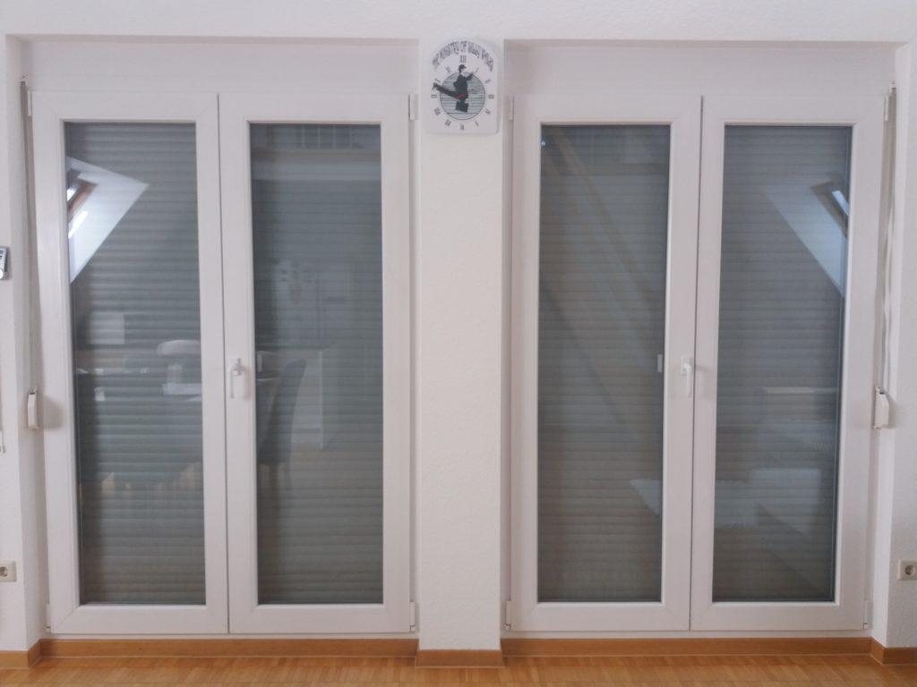 Portas de vidro, com persianas fechadas por fora, um relógio no meio.